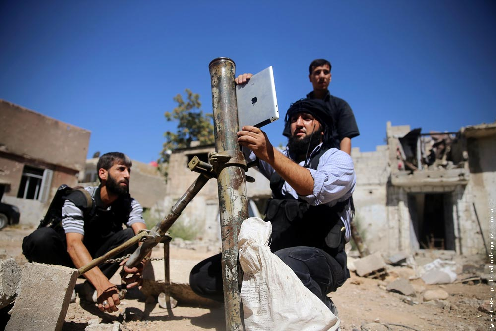 A member of the 'Ansar Dimachk' Brigade which operates under the Free Syrian Army uses an iPad during preparations to fire a homemade mortar in Jobar